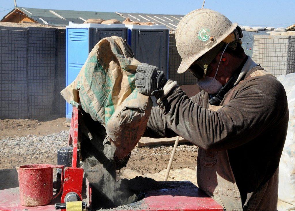 Obrero echando mortero de cemento en la mezcladora eléctrica