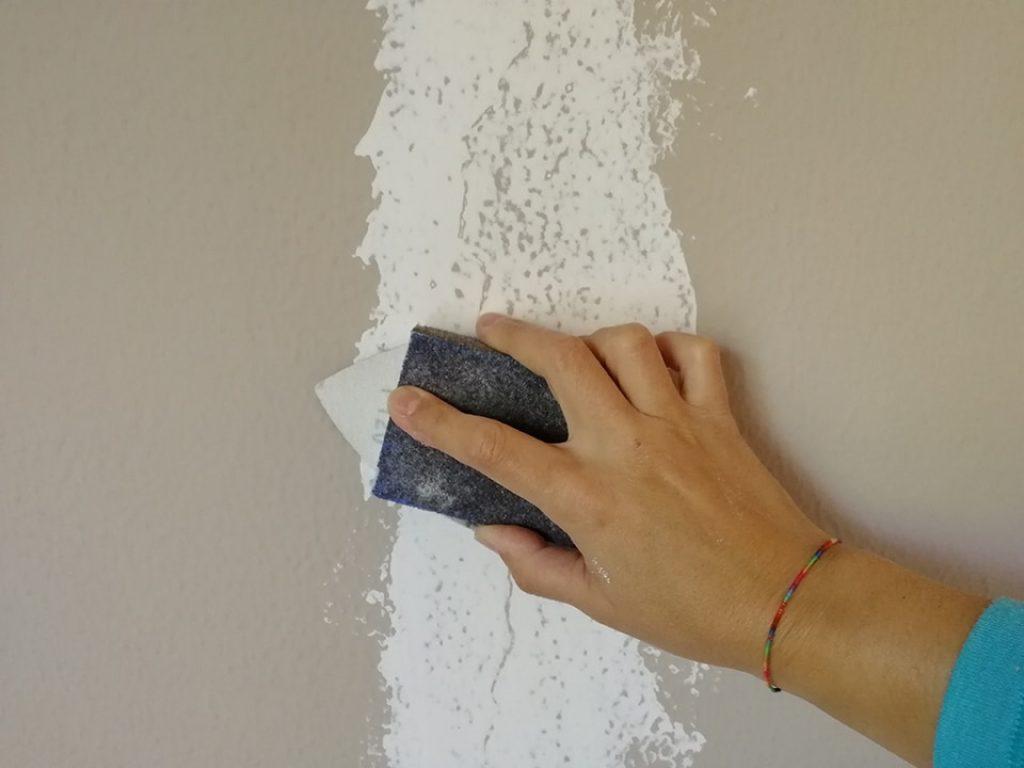 Lijando la pared reparada con yeso con un taco de lija