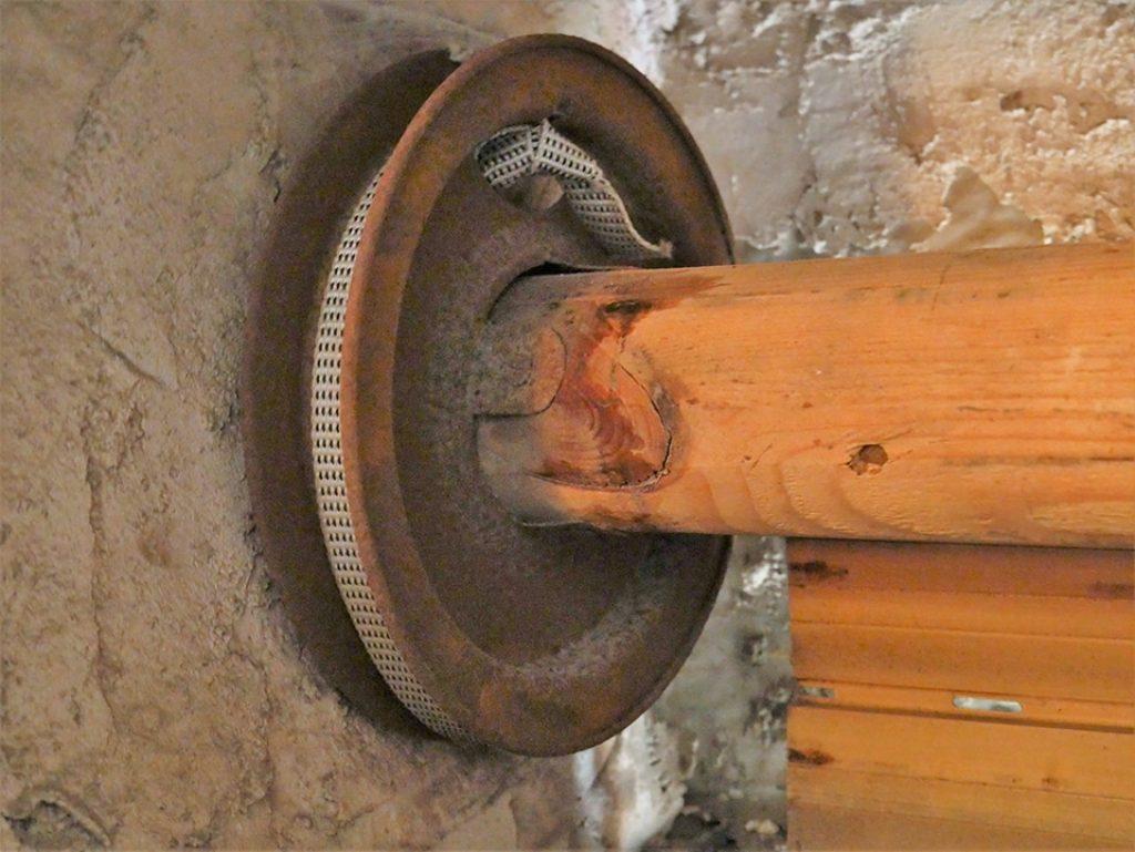 Vista de cerca de la polea de la persiana, con la cinta rota aun enrollada