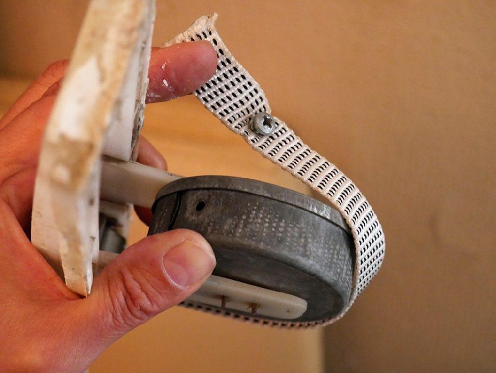 Coloca el extremo de la cinta en el recogedor y sujétala con el tornillo